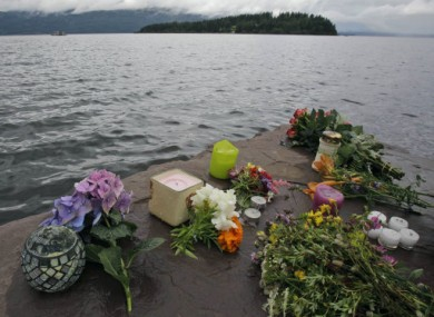 Flowers and candles left in memory of the victims of the shooting lie on the shore opposite Utoya.