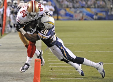 San Francisco 49ers wide receiver Josh Morgan is driven out of bounds by San Diego Chargers defensive back Antoine Cason.