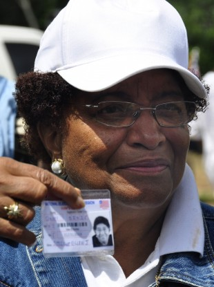 Incumbent president - and Nobel laureate - Ellen Johnson Sirleaf - displays her ID as she queues to vote in Tuesday's first round of balloting.