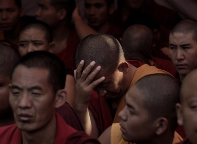 A Tibetan exile monk holds his head as he takes part in a day-long hunger strike in New Delhi, India, to express solidarity with the plight of the people in Tibet, Tuesday 18 October 2011.