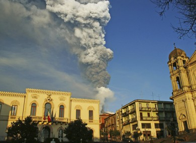 Smoke and ash billow from Mount Etna framed by the Sicilian town of Zafferana earlier today.