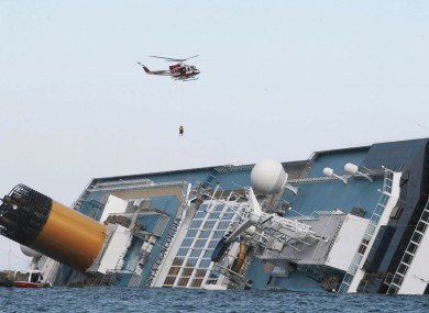 An Italian firefighter helicopter perfroms a rescue operation as it flies over the luxury cruise ship Costa Concordia which ran aground the tiny Tuscan island of Giglio, Italy