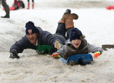 People sledge down Primrose Hill in London as heavy snowfall caused travel disruption across much of Britain today.