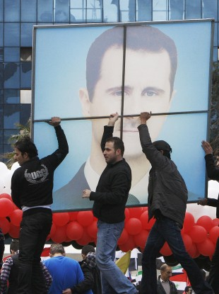 Pro-regime protesters carry a poster of Syrian President Bashar Assad during a rally in Damascus earlier today.