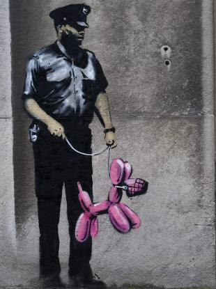 Graffiti from famed British graffiti artist Banksy is displayed on a wall in Toronto.