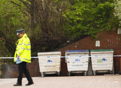 A Hampshire Police officer stands guard at the scene in Southampton where a burnt body was discovered in an industrial bin by firemen.