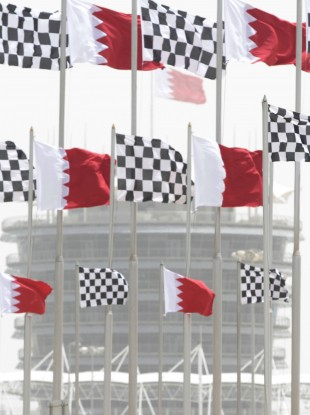 Dust envelops the Bahraini flag-topped tower of the Bahrain International Circuit in Sakhir, Bahrain.