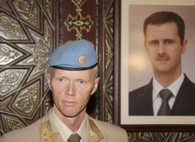 Maj Gen Robert Mood alongside a portrait of President Assad.