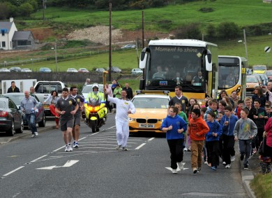 Olympic torchbearer 100 Ciaran Kinney carries the Olympic Flame on the Torch Relay leg between Ballygalley and Glenariff in the North today.