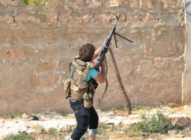 A Syrian rebel shoots towards a helicopter during clashes with government forces at Saraqeb yesterday.