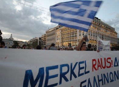 A protestor waves a Greek flag in Athens on Monday, Oct. 8, 2012 during an union anti-austerity rally a day before the visit by German Chancellor Angela Merkel.