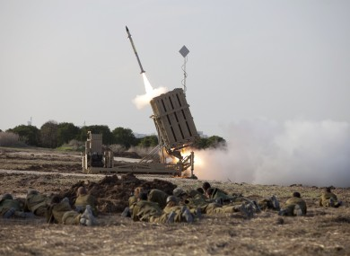Israeli soldiers lie on the ground as an Iron Dome missile is launched near the city of Ashdod