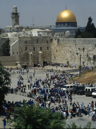 Israel, Jerusalem, Gold dome of the Aska Mosque and western or Wailing Wall with crowds of worshippers.