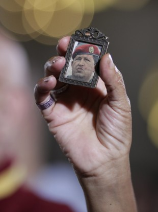 A woman holds up an image of Venezuela's President Hugo Chavez as people gather to pray for him at a church in Caracas, Venezuela.