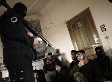 Syrian rebels listen to their trainer on how to use a rocket propelled grenade near Idlib, Syria