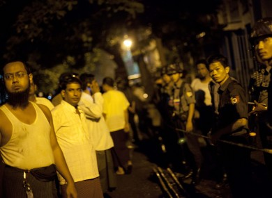 Police officers stand guard outside a mosque that a fire killed 13 children in Yangon, Myanmar.