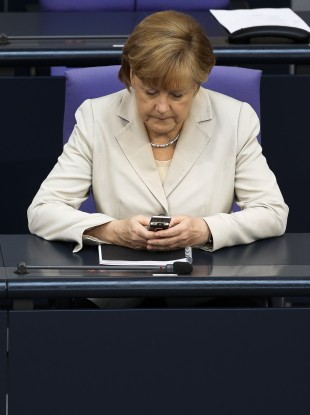 German Chancellor Angela Merkel uses her mobile phone.