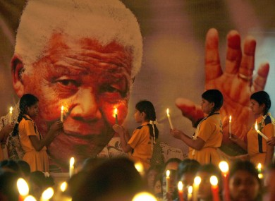 Schoolchildren hold candles near a giant portrait of former South African President Nelson Mandela in Chennai, India.