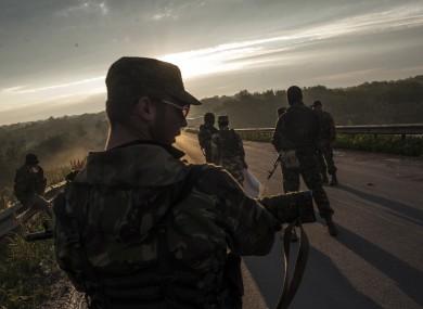 Pro-Russian fighters wait for representatives of the Ukrainian troops at a check point in the village of Karlivka near Donetsk.